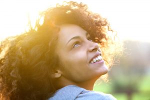 Woman smiling as sun shines from behind her