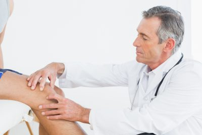 Doctor examining patient's knee