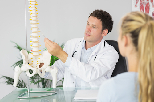Doctor explains back pain and chiropractic care with a model of a spine suspended on a rod.