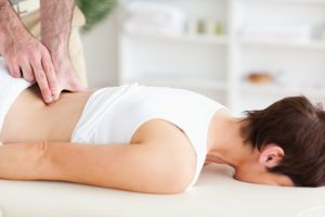 A chiropractor is massaging a woman, administering chiropractic care