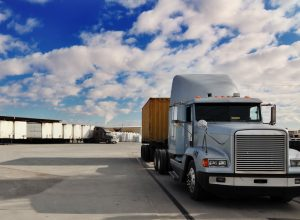 Semi Truck in shipping yard with nice blue sky and fluffy white clouds