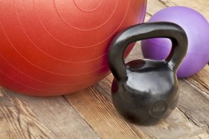 Black iron kettlebell, Swiss and medicine exercise balls on wooden deck - fitness concept